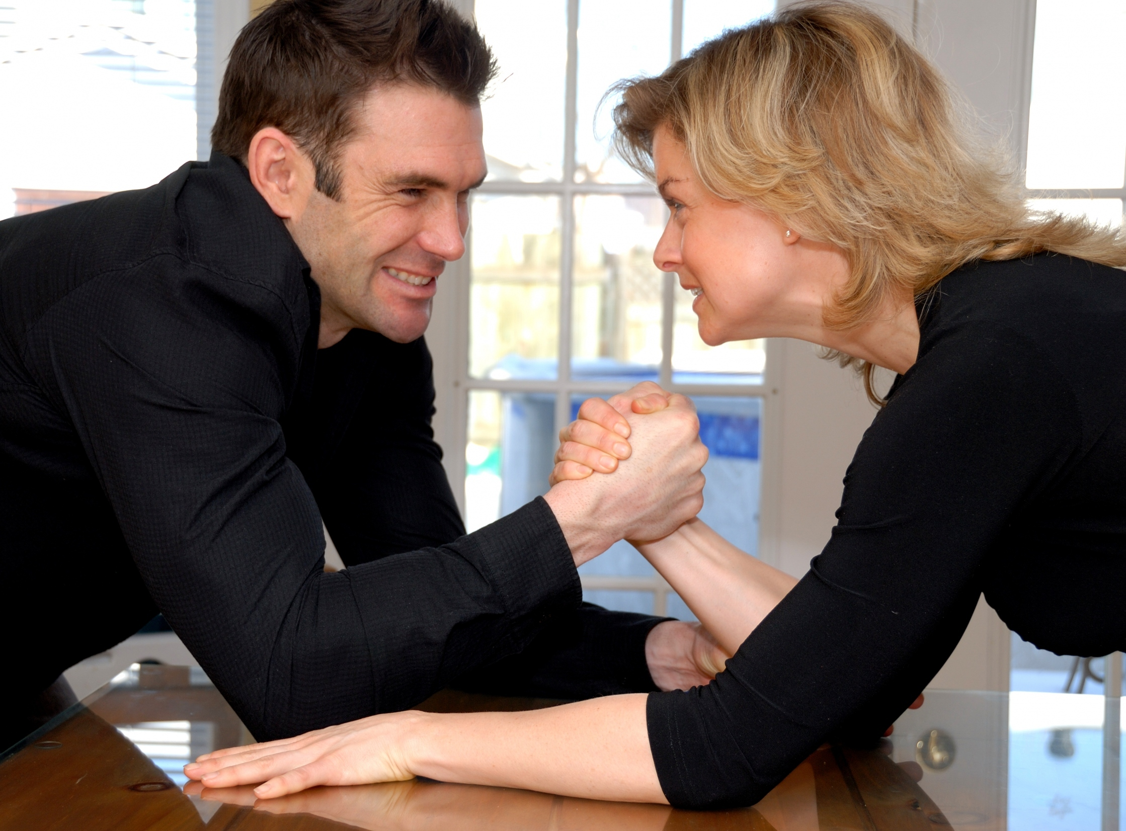 angry couple fighting with some arm wrestling